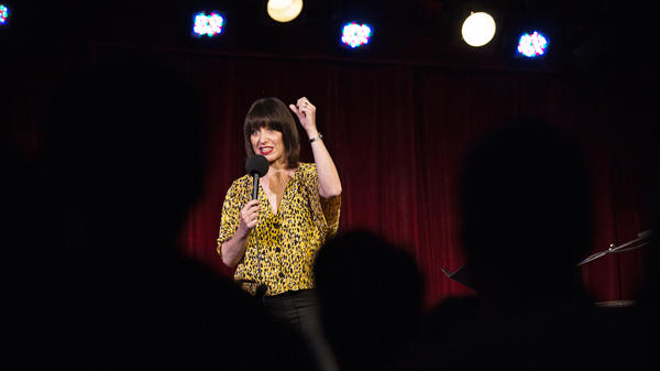 Ophira Eisenberg performs on stage on <em>Ask Me Another</em> at the Bell House in Brooklyn, New York.