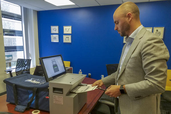 Clear Ballot CEO Jordan Esten places a ballot into the company's voting machine, which scans digital images of ballots and collects the paper copies in a bag. The images are stored on encrypted USB sticks, as the system is offline and has no modem. (Zeninjor Enwemeka/WBUR)