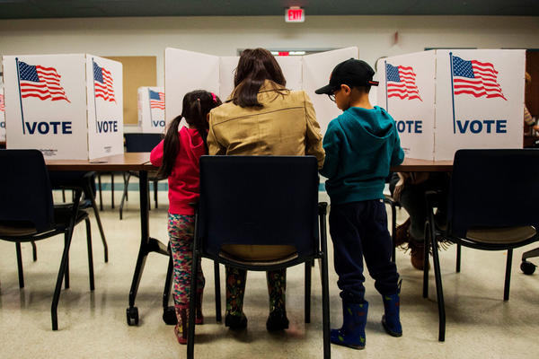 A woman and her children vote at a polling station during midterm elections at the Fairfax County bus garage in Lorton, Va.