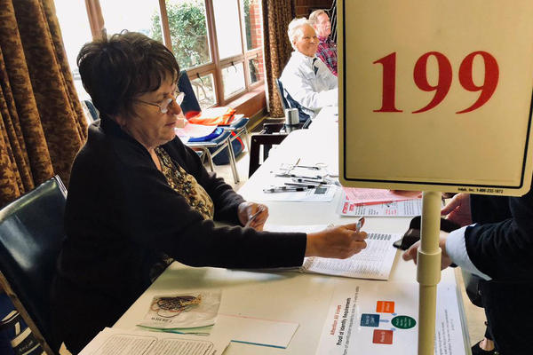 A poll worker checks in a voter at Crown Heights Christian Church in Oklahoma City