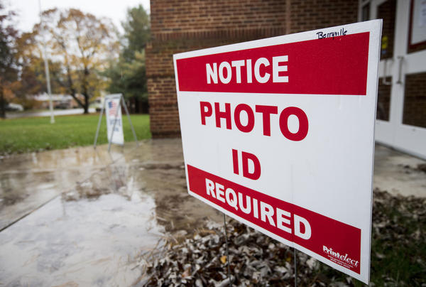 North Carolina will join Virginia and 17 other states that require voters to show a photo ID to vote. A sign notifies voters that a photo ID is required at the Clarke County Schools office polling location in Berryville, Va., on Nov. 6, 2018.