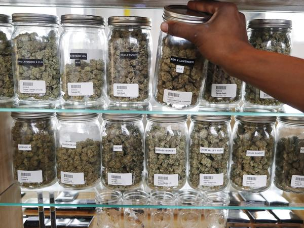 Michigan has become the first state in the Midwest to legalize recreational marijuana, after voters approved a ballot measure Tuesday. Here, a clerk reaches for a container of marijuana buds at Utopia Gardens, a medical marijuana dispensary in Detroit.
