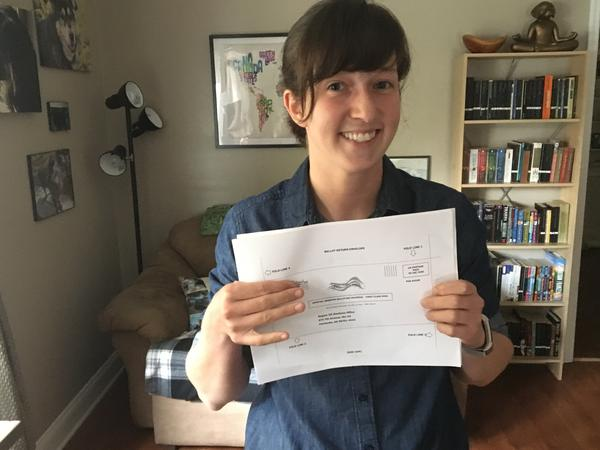 Kristin Backlund, whose husband is an Air Force ROTC instructor, holds her Alaska absentee ballot. She says obtaining and completing it was a complicated process.