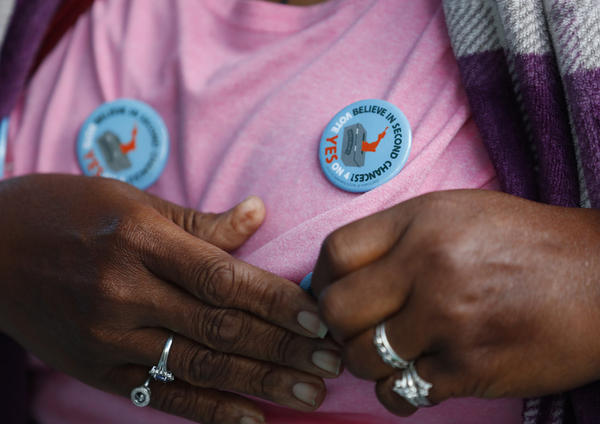 "Yvette Demerit puts on a button in support of Amendment 4 at the Ben & Jerry's ""Yes on 4"" truck at Charles Hadley Park in Miami on Oct. 22, 2018. The amendment asking voters to restore voting rights to people with past felony convictions passed on election night. (Wilfredo Lee/AP)"