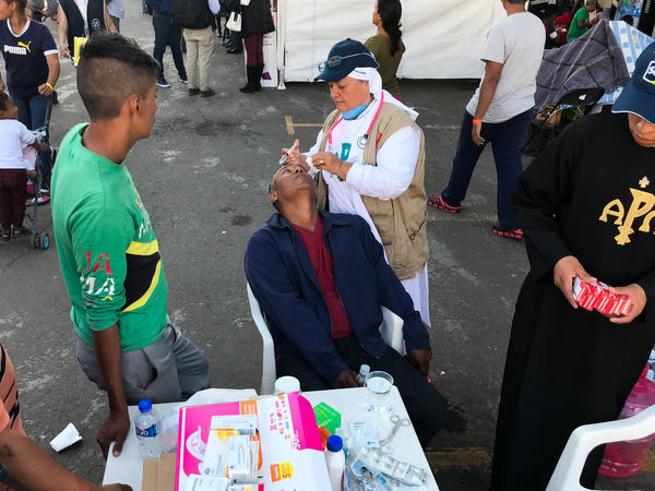 "Sister Bertha Lopez Chaves applies anti-inflammatory eyedrops to a migrant at a stadium in Mexico City where the caravan is resting. Her order is one of roughly 50 groups giving aid to the migrants in the Mexican capital. ""We're just trying to deal with their basic needs so they can continue on,"" she says."