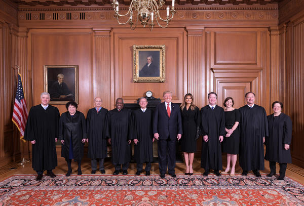 President Trump and first lady Melania Trump pose with Justice Brett M. Kavanaugh (fourth from right) and his wife, Ashley Kavanaugh, as well as other members of the Supreme Court in the justices' conference room before the investiture ceremony. Justice Ruth Bader Ginsburg was absent.