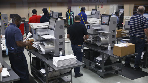Workers load ballots into machines at the Broward County Supervisor of Elections office in Lauderhill, Fla.