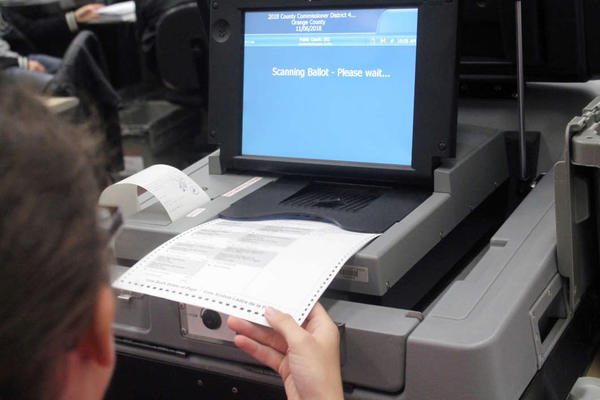 Victoria Fisher inserts ballots into ballot machine at the Orange County Supervisor of Elections. Recounting started Nov. 12 in Orange County.