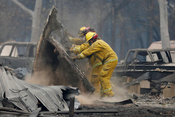 Cal Fire firefighters comb through a house destroyed by the Camp Fire in Paradise, Calif., on Tuesday.