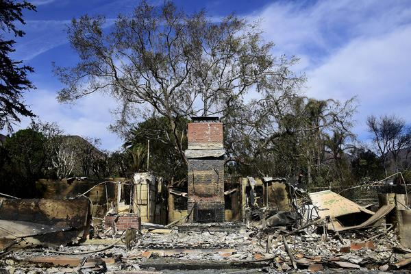 A fireplace and chimney are all that remains of a house in Malibu, Calif., on Tuesday. A group of volunteers are bringing in supplies for Malibu residents via a boat, the <em>Los Angeles Times</em> reports.