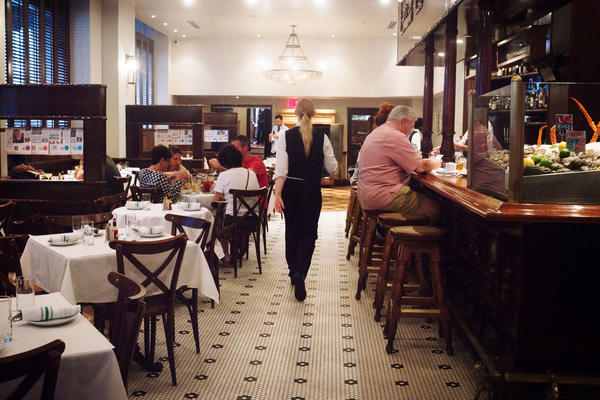 A member of the staff walks through Luke, one of the restaurants still owned by John Besh, on St. Charles Avenue in New Orleans.