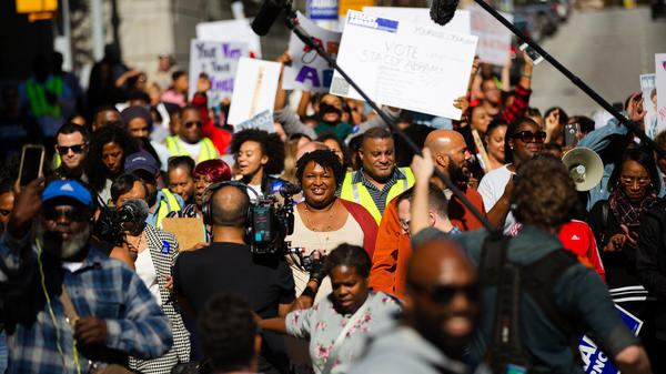 Stacey Abrams, then the Democratic nominee for governor of Georgia, center left, and musical artist Common, center right, lead a Souls to the Polls march in Atlanta, Ga., on Oct. 28, 2018.