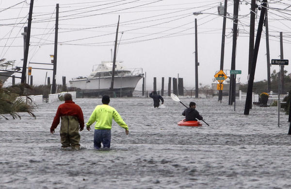 People wade and paddle down a flooded street as Storm Sandy approaches on Oct. 29, 2012, in Lindenhurst, N.Y. (Jason DeCrow/AP)