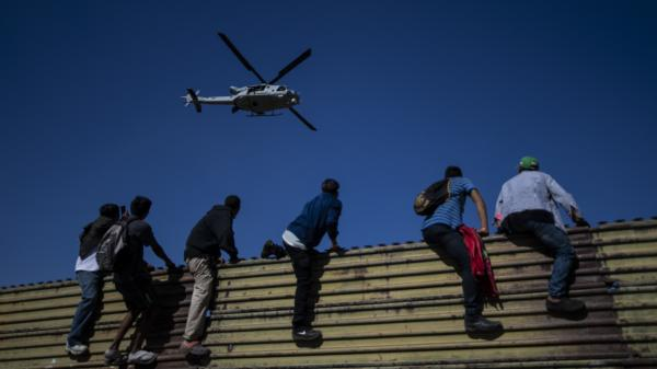 A group of Central American migrants climb a metal barrier on the Mexico-U.S. border in Tijuana on Sunday.