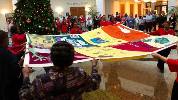 A quilt is unfurled at Jacksonville City Hall Monday.