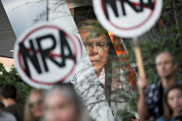 """Protesters gather beneath a banner featuring Wayne LaPierre, CEO of the National Rifle Association, during a rally outside the NRA's annual meeting in Dallas in May. When the NRA told doctors to """"stay in their lane"""" instead of weighing in on gun policies, Dr. Joseph Sakran used Twitter to express his outrage."""