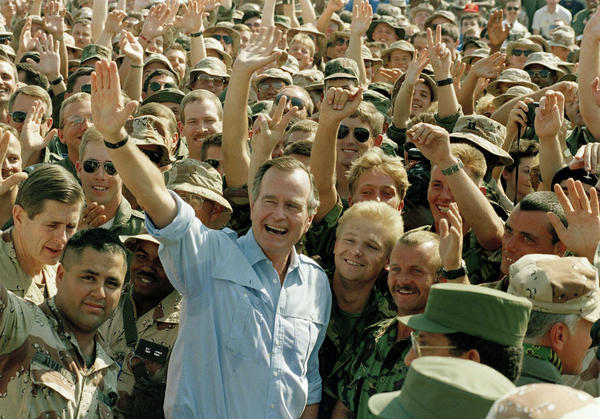 Bush poses with soldiers during a stop at an air base in Dhahran, Saudi Arabia, on Nov. 22, 1990.