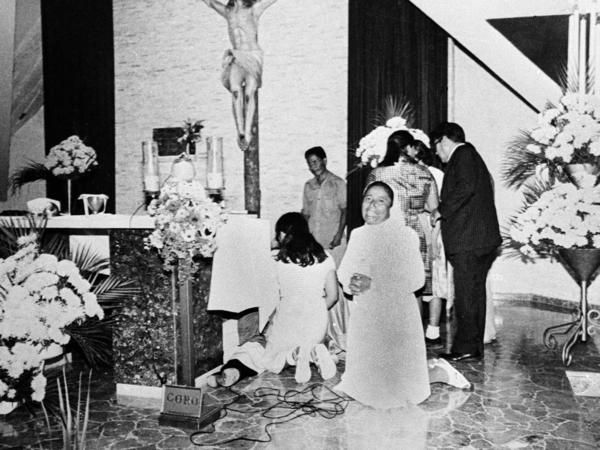 A nun clasps her hands in prayer as others gather around Romero after he was shot at the altar while celebrating Mass in 1980.