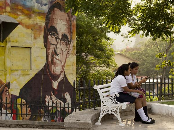 A mural depicting Romero decorates a wall where students sit in a plaza in Panchimalco, El Salvador, in 2015.