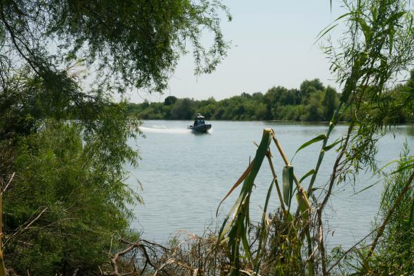 A U.S. Customs and Border Protection boat plies the waters of the Rio Grande near the edge of the National Butterfly Center.