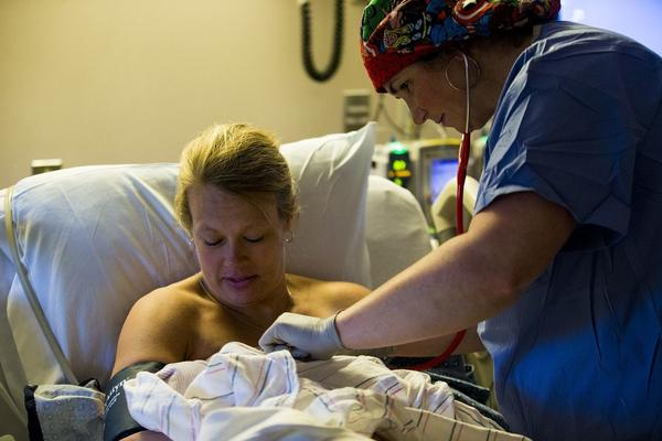 "A nurse checks the breastfeeding progress with Melisa and Brady. Melisa says she's grateful she was able to delivery both babies vaginally. ""I did not want to have a natural birth <em>and</em> a C-section,"" she says. ""That would be a brutal recovery."""