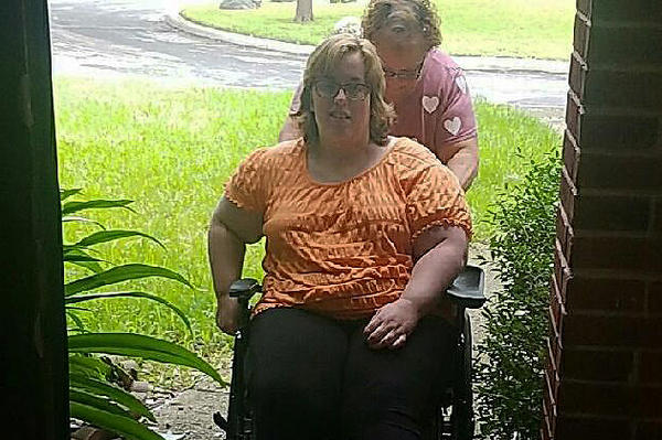 Navy veteran Whitney Hardin, 24, enters her home with help from her mother, Joy.
