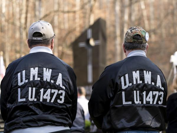 Two United Mine Workers of America members pay their respects to the 78 men who died during a memorial service Sunday in Mannington, W.Va.