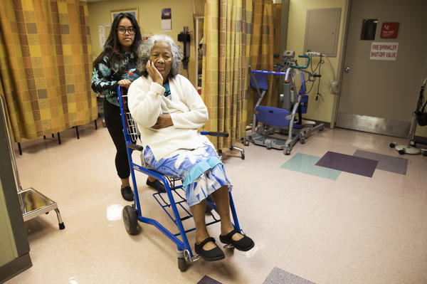 Daina Judah, 18, wheels her grandmother, Daina Joseia, out of an exam room at St. Mary's Hospital in Enid, Okla. Joseia checks in at the clinic weekly, so a health care provider can tend to a chronic sore on her back that's a medical complication of her diabetes.