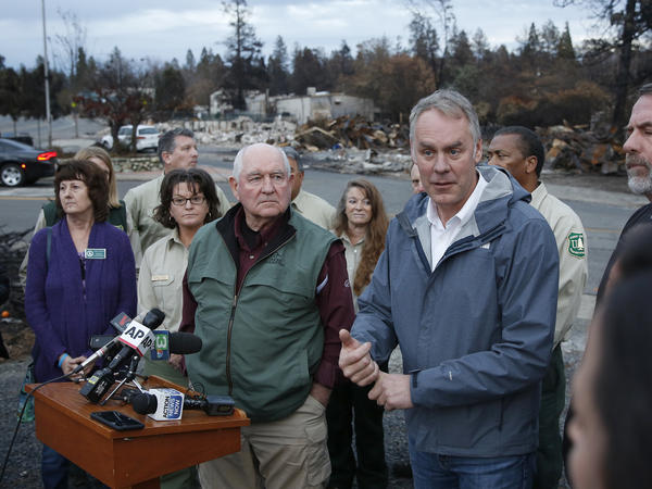 Interior Secretary Ryan Zinke, right, answers a reporters question after touring fire ravaged Paradise, Calif. with Agriculture Secretary Sonny Perdue, center. The pair advocated more aggressive forest management policies to mitigate damage from future wildfires.