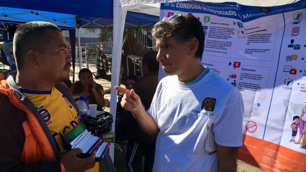 Jorge Bustamante of the UN High Commission for Refugees explains to a migrant the process for applying for asylum in Mexico.