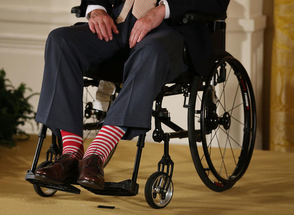 Bush wears red stripped socks as he sits in a wheelchair during an event in the East Room at the White House, July 15, 2013.