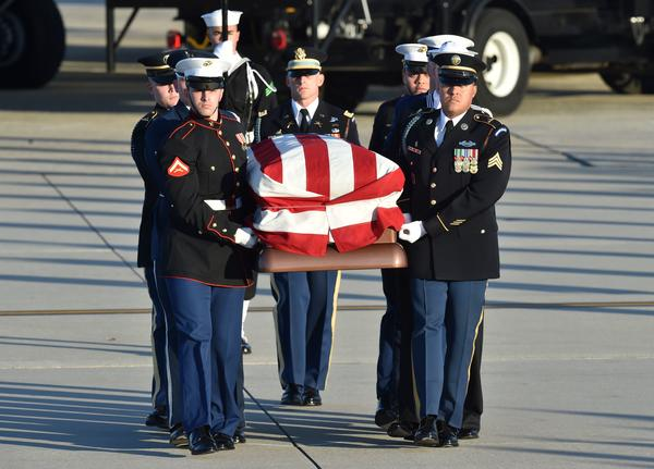 The flag-draped casket of former President George H.W. Bush is carried by a joint services military honor guard to the hearse at Joint Base Andrews, Md., on Monday.