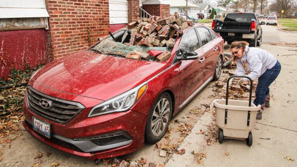 Valerie Coffey cleans up debris next to her house in Taylorville, Illinois. The December 1, 2018, tornado toppled her chimney onto her fiancé's car.