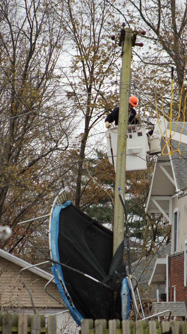 An Ameren employee works to repair power transmission lines in Taylorville on Sunday, December 2, 2018. Saturday's tornado felled trees, damaged roofs, and wrapped a trampoline around this utility pole.