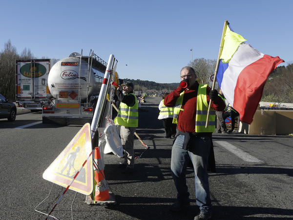"The French government is suspending a planned fuel tax hike, after ""yellow vest"" demonstrators took to the streets for months of protests. On a motorway near Aix-en-Provence, France, on Tuesday, demonstrators set up a barrier."