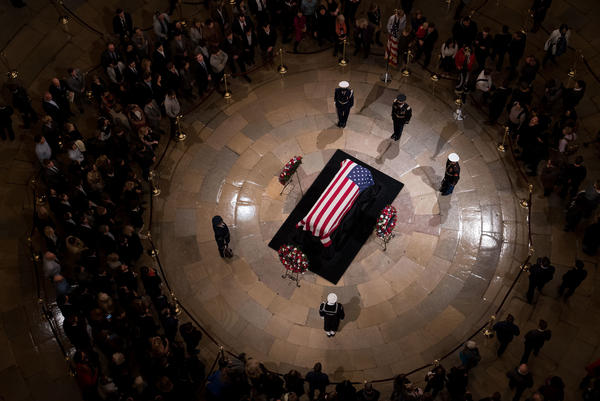 Members of the public view the casket containing former President George H.W. Bush's remains as he lies in state in the U.S. Capitol Rotunda on Monday night.