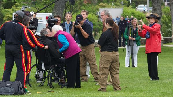 Barbara Bush greets Bush with a kiss after his successful skydive in 2014 in Kennebunkport, Maine to celebrate his 90th birthday.