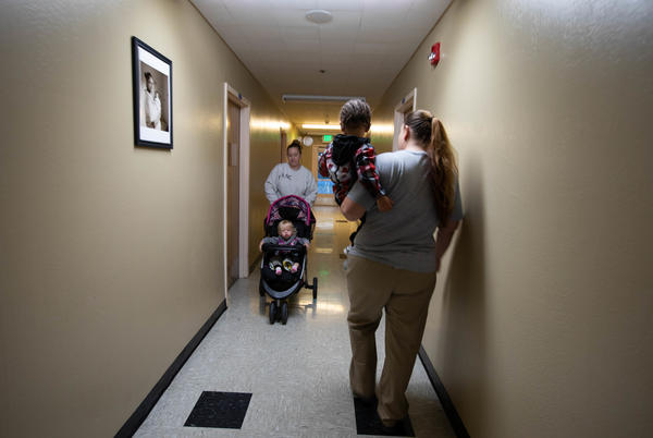 Crystal Lansdale, carries her son, Kirshawn, as they make their way to the in-prison daycare center before she heads to a work program.
