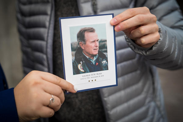 Grace Rector and Yuri Nesen, both sophomores at Georgetown University, hold up a card commemorating former President George H.W. Bush after visiting the Capitol.