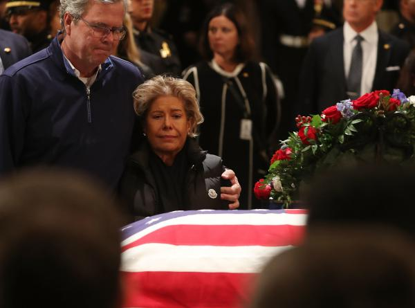 Former Florida Gov. Jeb Bush and his wife Columba Bush pay their respects in front of the casket of the late former President George H.W. Bush as he lies in state in the U.S. Capitol Rotunda Tuesday in Washington, D.C.