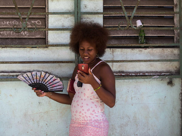 Cuba's telecom monopoly is rolling out broad Internet access for mobile phone users this week. Here, a woman uses her smartphone to surf the Internet in Havana.