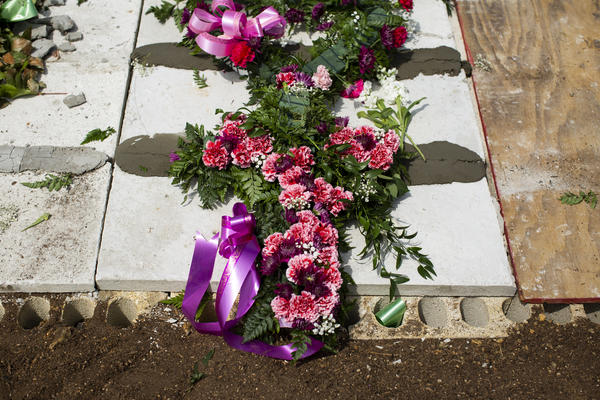 "Floral arrangements on Irizarry's tomb at the Remanso de Paz Municipal Cemetery in Camuy. ""She wanted to be buried near her mother and father,"" her son said. He laments not being able to fulfill that final wish."