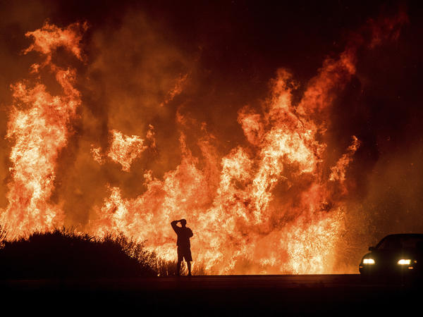 A motorists on Highway 101 watches flames from the Thomas fire leap above the roadway north of Ventura, Calif., in December 2017. Hundreds of homes were destroyed in what was then California's most destructive wildfire.