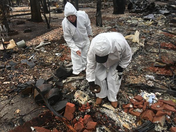 Jerry and Joyce McLean, wearing hazmat suits, look for sentimental items as they sift through the remains of their home Wednesday in Paradise, Calif.