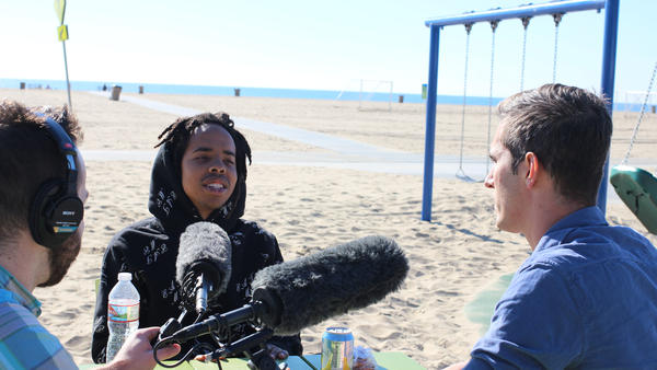 Thebe Kgositsile, known as Earl Sweatshirt, and NPR's Ari Shapiro speak on the beach in Santa Monica.