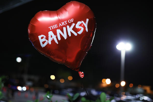 "A promotional balloon — styled after the red, heart-shaped balloon in one of Banksy's famous artworks — floats at the grand opening of<a href=""https://www.banksyexhibit.com/""> The Art Of Banksy</a> show in Miami."