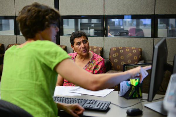 Anita Hoffman works with Elizabeth Colvin, director of Foundation Communities, to sign up for a health insurance plan on June 17, 2015.