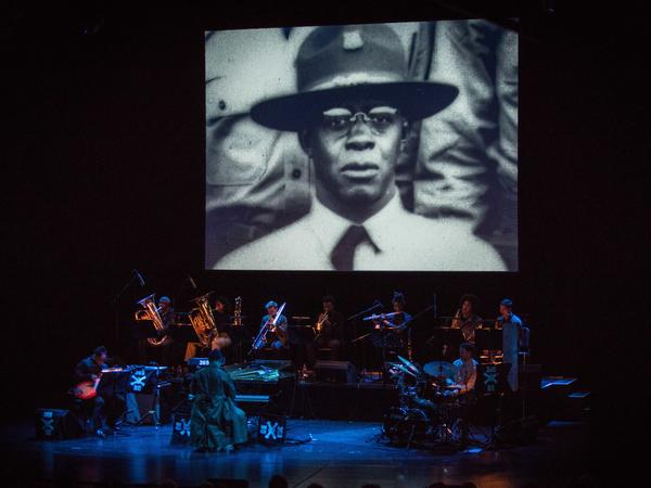 A photograph of jazz pianist James Reese Europe projected above the musicians performing Jason Moran's <em>James Reese Europe and the Absence of Ruin</em>.