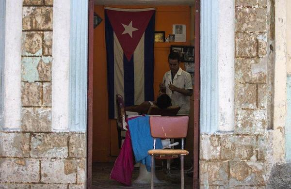 A Cuban barber shaves a customer at his privately owned business in Havana.