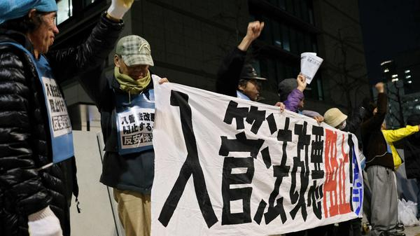 In front of Japan's parliament on Friday, people stage a rally against the bill to allow more foreign workers into the country.